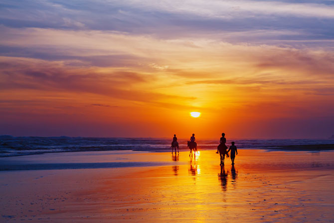 Reiten am Strand im Sonnenuntergang