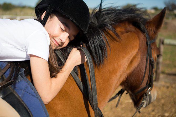 Glückliches Kind auf Pferd in den reiterferien