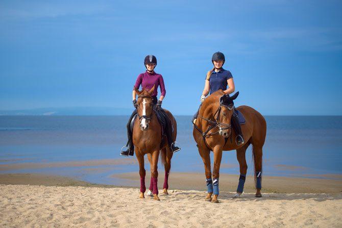 Reiter mit Pferden am Strand